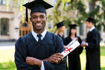 30344849-happy-graduate-happy-african-man-in-graduation-gowns-holding-diploma-and-smiling-while-his-friends-s
